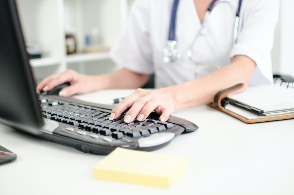 doctor's hands on keyboard completing hipaa compliance